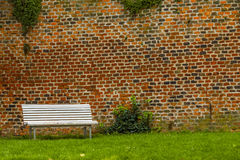 White bench standing in front of an old brick wall in a city park. Stock Images