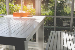 white bench and table beside glass door with garden view Stock Photos