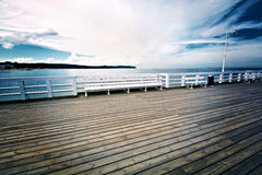 White bench on wooden pier in Sopot, Poland. Royalty Free Stock Photos