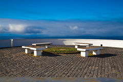 White benches. On the view on the rock on Azores Stock Photos