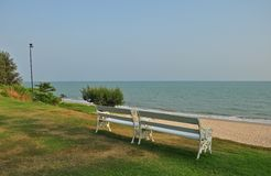 White benches on the beach in front of the sea. With evening sun light, wait for guess to sit in Stock Photography