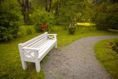 White benches in a green garden. Horizontal royalty free stock images