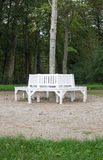 White benches. Grouped around a tree Royalty Free Stock Image