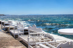 White benches oceanside in Greece. White benches line a sidewalk next to the ocean in Mykonos, Greece Stock Photo