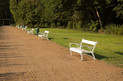 White benches in the park. Park benches along the sandy path royalty free stock photos