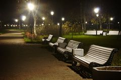 White benches in the park night time. With Vignette and glow. White benches and streetlamp in the park night time. Vignette version with glow Royalty Free Stock Photography