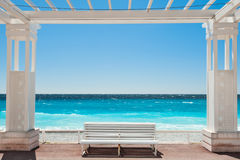 White benches on the Promenade des Anglais in Nice, France. Beautiful turquoise sea and beach stock images