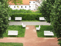 White benches. Some nice white benches and green trees in the park in Brno, Czech Republic in spring Royalty Free Stock Photos
