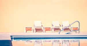 White benches by swimming pool stock photo
