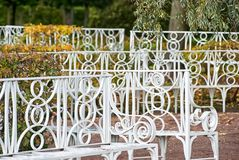 White benches. Tsarskoye Selo. Saint-Petersburg. Russia. TSARSKOYE SELO, SAINT-PETERSBURG, RUSSIA - OCTOBER 7, 2017: White benches in the autumn Catherine Park Stock Photography