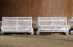 White Benches. White wire mesh benches against a pebbled stone wall Royalty Free Stock Photography