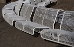White Benches. White wire mesh benches against a pebbled stone wall Stock Photo