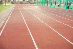 White bent lines marking red stadium with soft covering Royalty Free Stock Image