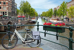 White Bicycle on a Bridge Overlooking a Canal in Amsterdam against Blue Sky Royalty Free Stock Photography