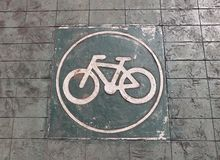 The white bicycle in the circle painting on the green bike lane stock image