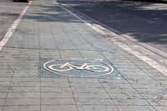 The white bicycle in the circle painting on the green bike lane. It is a division of a road marked off with painted lines, for use by cyclists stock photos