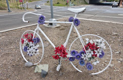 White Bicycle Decorated with Blue and Red Flower shapes at an In. White ten speed bicycle adorned with red and blue flower shapes at an intersection near a Stock Photo