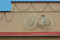 White bicycle hanging on wall of house near the roof Royalty Free Stock Photo