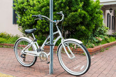 White Bicycle Locked to a Sign Post Stock Images