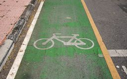The white bicycle painting on the green bike lane. it is a division of a road marked off with painted lines. The white bicycle painting on the green bike lane stock image