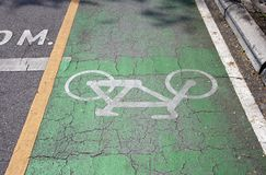 The white bicycle painting on the green bike lane. it is a division of a road marked off with painted lines. The white bicycle painting on the green bike lane stock photos