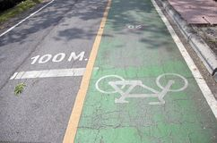 The white bicycle painting on the green bike lane on the line of 100 meters distance. It is a division of a road marked off with painted lines, for use by Stock Photos