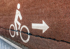 White bicycle road sign on asphalt lane with arrow symbol in vin Stock Photos