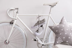 White bicycle and sneakers. Close-up of white old bicycle with sneakers in room Stock Images