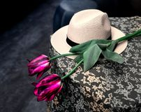 White biege woman hat and rose flower on the top of table with tablecloth. Concept of waiting for romantic true love and dating. White biege woman hat and rose stock photography