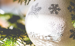 White big bauble with silver snow flakes on Christmas tree close Stock Images