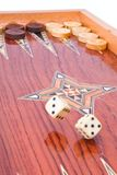 White big dices fall on handmade backgammon board. Two big ivory dices falling on wooden handmade backgammon board with chips and on white background Stock Image