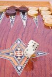 White big dices falling on wooden backgammon board. Two big ivory dices falling on wooden handmade backgammon board with chips and on white background Stock Images