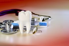 White big healthy tooth and different tools for dental care, on gradient dental background with stethoscope. White big healthy tooth and different tools for royalty free stock photo