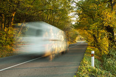 White big moving car on road in the nature. Moving blurred car on asphalt road under the trees royalty free stock image