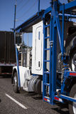 White big rig car hauler with two levels trailer run with car on. A classic simple powerful bright white big rig semi truck with a two-tier car hauler trailer royalty free stock image