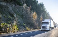 White big rig semi truck with dry van semi trailer driving in front of another semi trucks and cars traffic on wide highway. Big rig bright white classic semi stock image