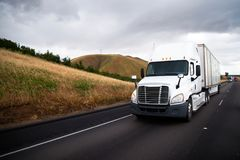 White big rig semi truck with dry van semi trailer driving in st. White big rig semi truck with dry van semi trailer driving in front of another traffic of semi royalty free stock images