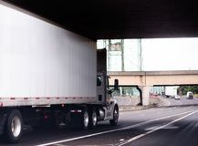 White big rig semi truck with day cab and dry van trailer runnin Stock Photos