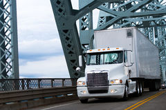 White Big rig semi truck and reefer on farm bridge Stock Images