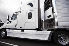 White big rig semi truck with reefer semi trailer and refrigerat. White bonnet American big rig semi truck with reefer semi trailer and refrigerator unit on it Royalty Free Stock Image
