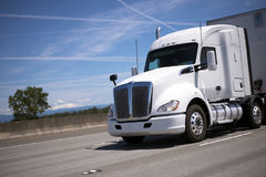 White big rig semi truck with semi trailer driving by wide inter. A beautiful powerful professional big rig semi truck with a large comfortable cabin and a super stock image