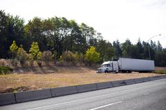White big rig semi truck tractor with reefer trailer going out o Royalty Free Stock Image