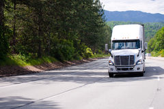 White big rig semi truck with trailer driving by wide multi-line. White modern big rig semi truck with chrome grille and dry van trailer driving by wide multi Stock Photography