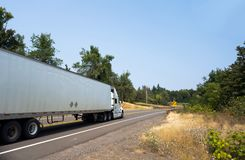 White big rig semi truck transporting cargo in dry van semi trailer on winding green road. White powerful big rig semi truck tractor transporting goods in dry royalty free stock photography
