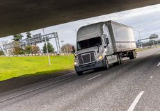 White big rig semi truck transporting industrial cargo on dry van semi trailer running under the bridge across the wide highway royalty free stock photos