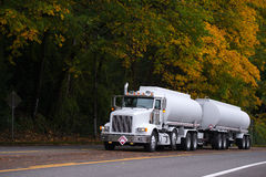 White big rig semi truck with two tank trailers on autumn road Royalty Free Stock Photo