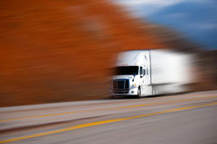 White big semi truck on the road on blurred colors background Stock Photos