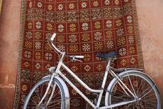 White bike in front of a traditional carpet Stock Photos