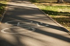 White bike path sign in the park. Image of a bicycle on the track, indicating the sign of traffic for cyclists Stock Photography