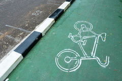White bike symbol on the green pavement in Thailand. White bike symbol on the green pavement in Thailand Stock Photography